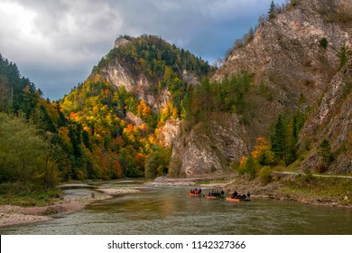 Raft with tourists floating along Dunajec gorge in Pieniny National Park., Poland at sunny autumn day. Dunajec river - popular tourist spot for boat rafting in Poland