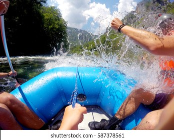 Rafting on a mountain river. Waves with spray and foam crashing on the side of the boat, and people rowing oars. Extreme sport