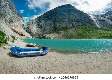Rafts boats on the lake in Briksdalsbreen valley in Norwegian Jostedalsbreen National Park.