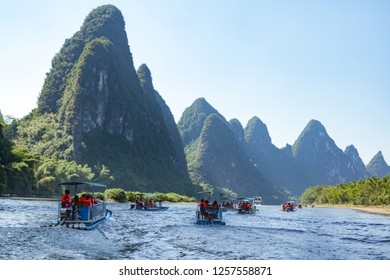 Rafts on Li River tour in Guilin, China. Two rafts on the river with striking green karst limestone cliffs in the background.