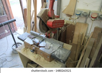 Ragalna - Italy / Aug 10, 2019. This is the circular mitre saw in the wood workshop of the village. It is equipped with protections and can be moved down with a handle onto the work piece.