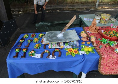 Ragalna - Italy / July 14, 2019. Several pictures of the art market on the parking place of the municipal building of Ragalna during the festival of the arancino. Here a ceramic art stand with statues