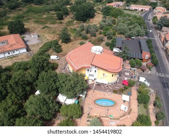 Ragalna - Italy / July 14, 2019. A west side drone view of the Ragalna (Sicily) municipality building, on the slopes of the Etna. Preparations for the Festival of the Arancino (a traditional snack).