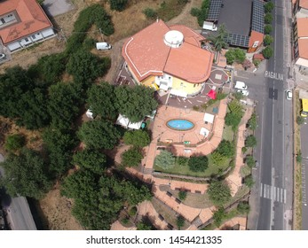 Ragalna - Italy / July 14, 2019. A west side drone view of the Ragalna (Sicily) municipality building, on the slopes of Mount Etna. Preparations for the Festival of the Arancino (a traditional snack).