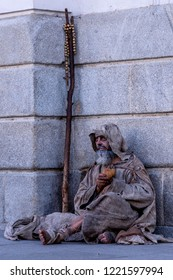 Ragged beggar begging on the street