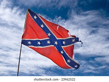 ragged confederate flag flying against sky