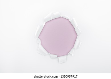 ragged hole in textured white paper on light purple background