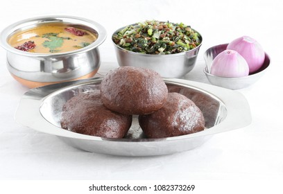 Ragi or finger millet balls, which are a healthy southern Indian food, in a tray with sambar and horse gram-amaranth leaves curry.