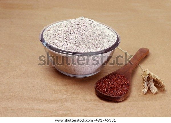 Ragi or finger millet flour in a glass bowl and ragi on a wooden spoon, and stalk, on a brown paper background.