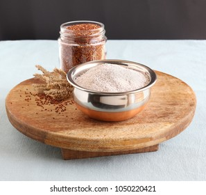 Ragi flour, which is gluten-free, in a bowl, and in the background is a bottle with ragi, which is also known as finger millet, and dried stalks.
