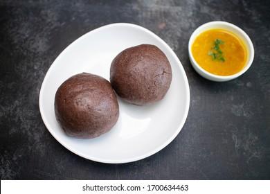 Ragi Mudde, Ragi sangati or finger millet balls and Toor dal Sambar healthy snack in Karnataka, India. Top view of traditional south Indian food on dark black background.