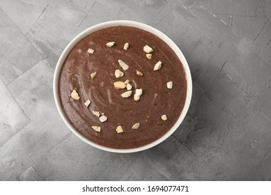 Ragi Porridge, Sweet Ragi Malt, Java healthy nutritional drink made from organic finger millet flour in a bowl garnished with crushed dry fruits,  Kerala, India. Top view Indian food grey background.