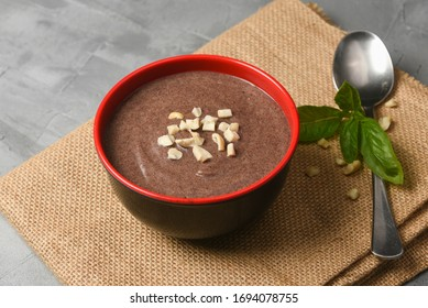 Ragi Porridge, Sweet Ragi Malt, Java healthy nutritional drink made from organic finger millet flour in a bowl garnished with crushed dry fruits,  Kerala, India. Top view Indian food jute background.