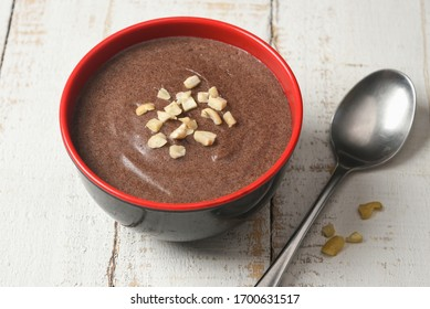 Ragi Porridge, Sweet Ragi Malt, Java healthy nutritional drink made from organic finger millet flour in a bowl garnished with crushed dry fruits,  Kerala, India. Top view Indian food white background.