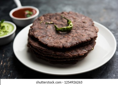 Ragi roti or flat Bread made using finger millet is a healthy and tasty breakfast dish of Karnataka, India. served with green chilli and chutney. selective focus