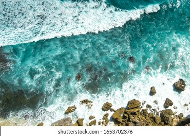 Raging blue waves of the ocean run and break on the rocks, top view