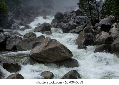 Raging waters from the Yosemite Falls, gushing over the granite boulders