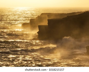 Raging waves against jagged cliffs at sunset
