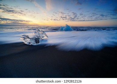 Raging waves smashing ice blocks at sunrise on Diamond Beach.