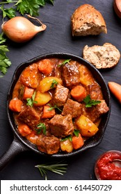 Ragout, goulash in frying pan on dark background, top view