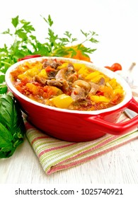 Ragout of turkey meat, tomato, yellow sweet pepper and onion with sauce in a brazier on a towel against the backdrop of a light wooden board