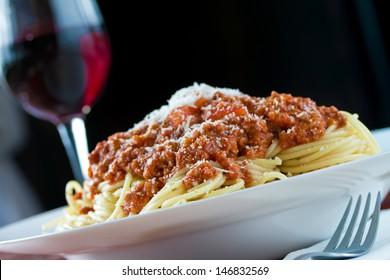 Ragu alla bolognese a complex sauce with spaghetti pasta and glass of red wine