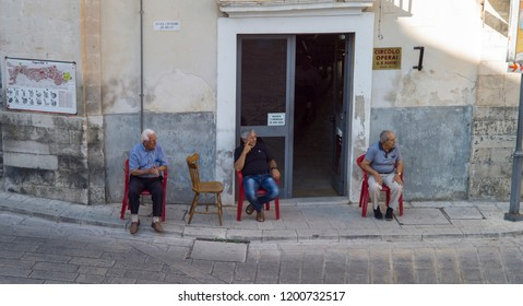 Ragusa, Italy - June 30 2017: The old people is relaxing in the narrow cobblestone street in the historic town Ragusa in Sicily.