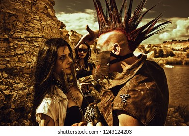 Raider with mohawk hairstyle, young pretty slave  in iron mask and slave trader posing over post-apocalyptic wasteland.