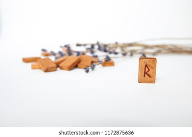 Raido. Scandinavian runes. Wooden runes on a table on a white background.