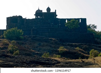 Raigad Maharashtra India February 25 2009 Silhouettes of samadhi(mausoleum) of a King shivaji maharaj and jagdishwar temple  at fort