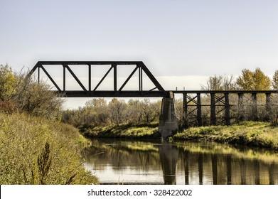 A rail bridge that crosses the narrow Battle River of Saskatchewan
