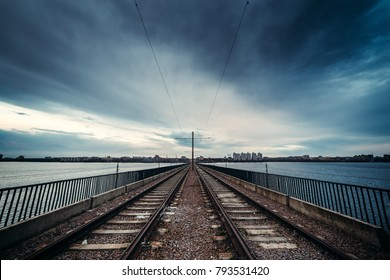 Rail road through the bridge with dramatic cloudy blue sky background over city, perspective, North Bridge in Voronezh, Russia
