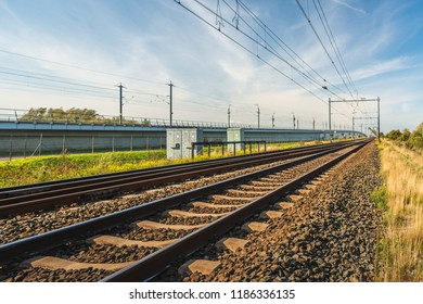 Rail tracks on sleepers and basalt gravel in the Netherlands. The photo was taken on a sunny summer day near the Moerdijk railway bridge. In the background is the rail section of the HSL railway line.