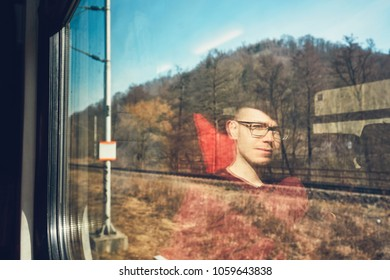 Rail transportation in sunny day. Pensive young man traveling seen though train window with reflection.