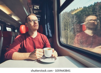 Rail transportation in sunny day. Pensive young man holding a cup of coffee traveling by train.