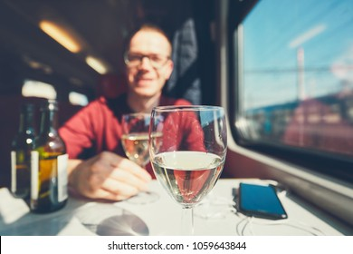 Rail transportation in sunny day. Smiling young man drinking wine wine on passenger train. Selective focus on the wineglass.
