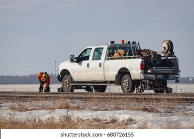 A rail worker is working on track beside a white pickup rail truck