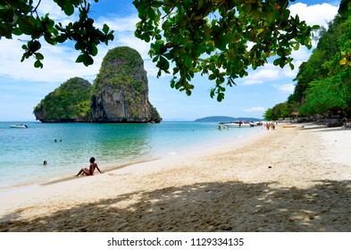 Railay, Thailand, April 28, 2015 - Tourists on the South end of Phra Nang beach with a big limestone boulder in the sea in the background.