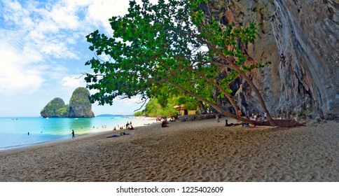 Railay, Thailand -April 28, 2015; Tourists on the South end of Phra Nang beach with the cliff on the right and big limestone boulders in the sea in the background.