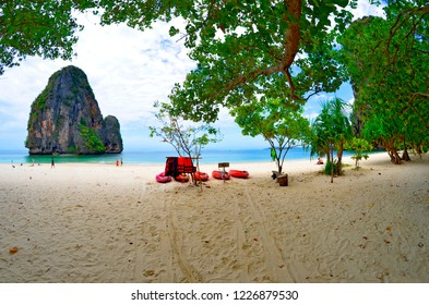 Railay, Thailand, April 28, 2015 - Tourists on the North end of Phra Nang beach with limestone boulders in the Andaman Sea.