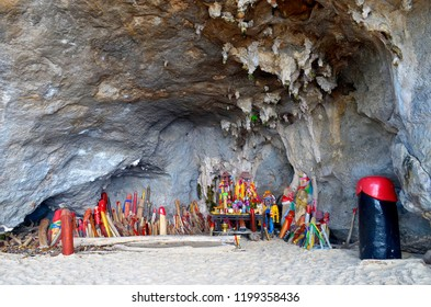 Railay, Thailand, October 24, 2014 - Candles, floral garlands and other offerings among the phallus shaped figurines of the Phra Nang Princess Cave.