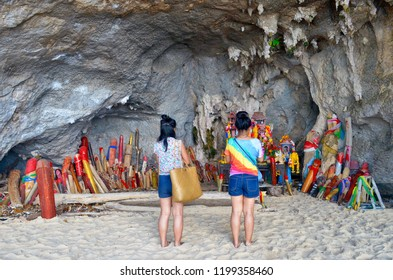 Railay, Thailand, October 24, 2014 - Two young Thai women praying in front of the phallus shaped figurines of the Phra Nang Princess Cave.