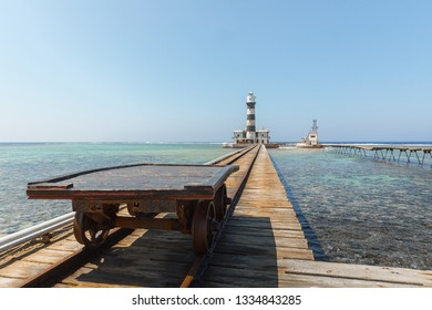 Railcart on pier with lighthouse