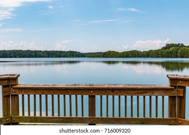 Railing of fishing pier with a view of the lake at Stumpy Lake Natural Area in Virginia Beach, Virginia.
