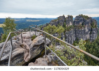 railing on beautiful old rocks and forest on background in Bastei, Germany