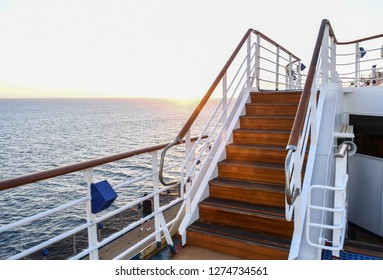 Railing and stairs of a cruise ship at sunset.