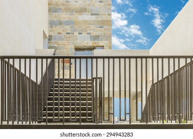 Railing and stone facade of building.
