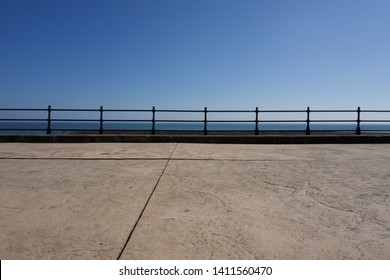 Railings along promenade at Scarborough under a clear blue sky