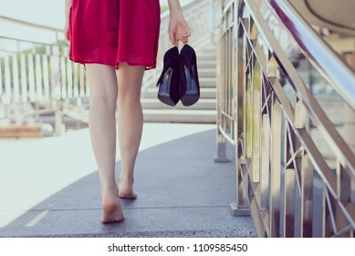 Railings balcony terrace direction future blister problem discomfort sidewalk concept. Rear behind back close up photo of happy careless carefree lady carrying pumps in hand, blurred background