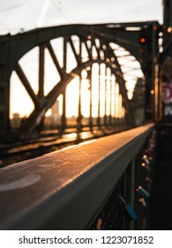 Railings of a bridge at sunset, with bridge blurred in background. Cologne, Germany.